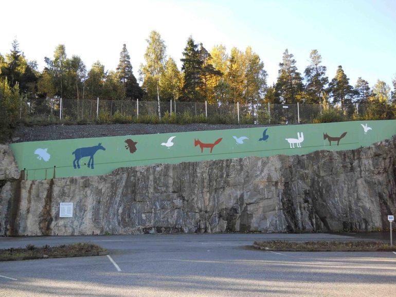 Rauman Kuvataidekoulun oppilaiden teos Metsän paraati Rauman Metsä Fibren parkkipaikan muurissa