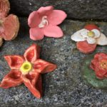 Rauman kuvataidekoulu 2018 oppilaiden keraamisia kukkia kiviportaalla