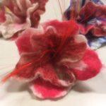 Edessä punasävyinen kukka, takana vasemmalla punasävyinen ja oikealla lilansävyinen kukka