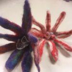 Tähtikukat, vasemmalla violetti, oikealla punainen, keskustassa hopeaa