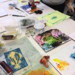 Taidegrafiikkaa vedostetaan, vedostuspöydällä värejä, taidegrafiikan teloja ja vedoslevyjä