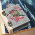 kirjamuotoinen puurasia kanteen maalattu punatulkkuja