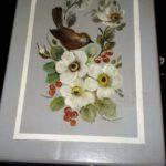 Koristemaalaus puurasia kuviona lintu ja valkoisia kukkia