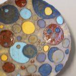 Laakea keramiikkavati pallokuvioita,väreinä harmaa, punainen, turkoosi, vihreä, sininen, keltainen ja violetti