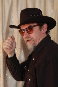 Kirjailijalla cowboyhattu ja aurinkolasit päässä.