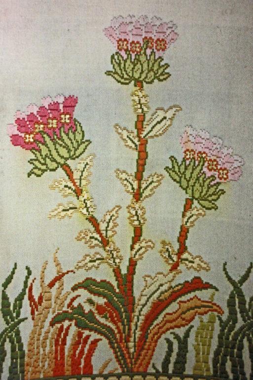 Yksityiskohta sermin kirjonnasta, kolme pitkävartista kukkaa.