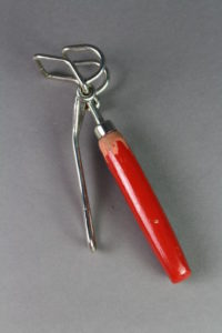 Kuuman astian nostopihdit. Metallinen pihtiosa ja punainen puinen varsi.
