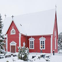 Lapin punainen kirkko lumisessa maisemassa.