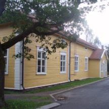 Vaaleankeltainen Vanha opisto -rakennus kesällä.