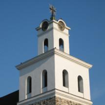 Pyhän Ristin kirkko valkoinen torni sinitaivasta vasten.