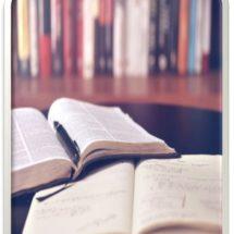 Kirjat avoinna pöydällä.