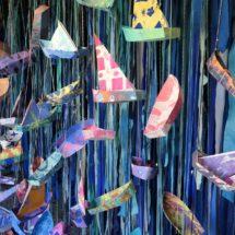 Taiteilija Lelia Byronin installaatio Vedet, jotka veneitämme yhdistää. Pienet paperiveneet roikkuvat tummansinistä taustaa vasten.
