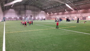 Pieniä lapsia pelaamassa jalkapalloa talviharjoitteluhallissa.