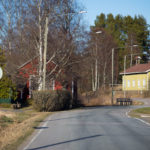 Vasaraisten asuinalueen läpi kulkeva tie. Taustalla taloja.