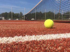 Tennispallo tenniskentällä kuvattuna verkon vieressä.