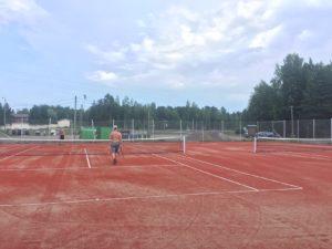 Lähdepellon tenniskenttä, jossa kaksi poikaa pelaa.