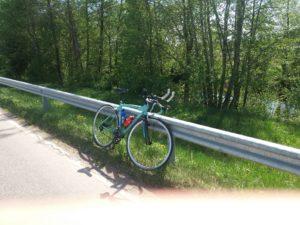 Maantiepyörä nojaa maantiekaidetta vasten.