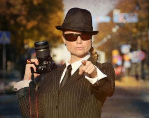 Rauma-agentti osoittaa sormella kohti kuvaajaa ja pitää toisessa kädessään olalla kameraa.