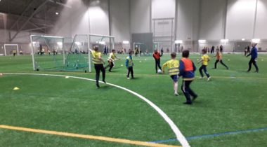 Iltapäiväkerholaiset pelaavat jalkapalloa talviharjoitteluhallissa