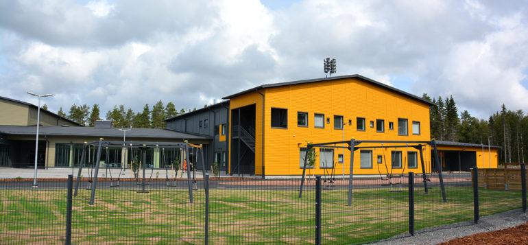 Pohjoiskehän koulun pihan leikkivälineitä etualalla, taustalla koulun keltainen kortteli.