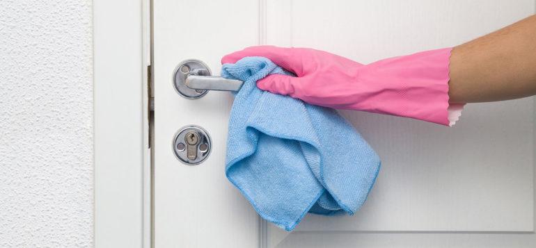 Käsi pyyhkimässä ovenkahvaa rätillä.