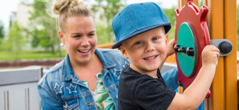 Poika leikkimässä kipparinpuistossa ja ohjaamassa laivanruoria lasten kiipeilytelineessä. Taustalla pojan äiti.
