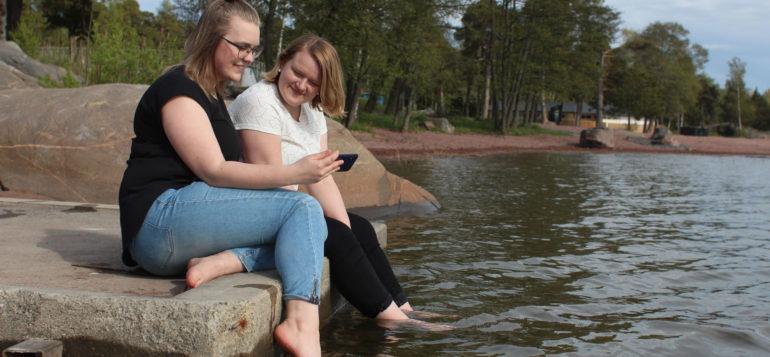 Sanni Tuuppa ja Meri Lehto istuvat kivellä meren rannalla.